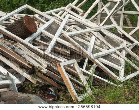 An Old Broken Window Frames Piled Together On Green Grass. A Lot Of Wooden Window Casements With Bli