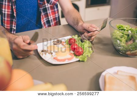 A Picture Of Tasty Omlet With Letuce And Cherry Tomatoes On Plate On Table. Guy Holds Knife And Fork
