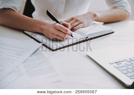 Closeup Young Business Woman Making Notes At Work. Close Up Of Businesswoman Sitting At Desk And Wri