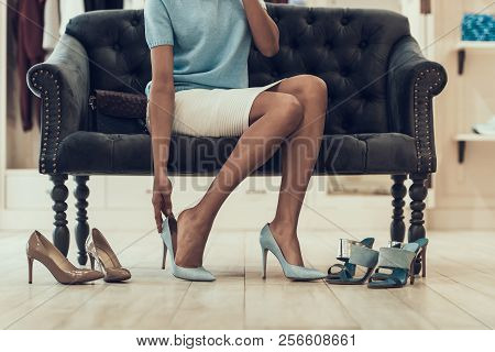 Closeup Of Young Woman Trying On Shoes In Store. Beautiful Black Girl Choosing Shoes To Buy In Bouti