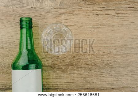 top view of soju bottle with glass on the wooden table. Soju is the colorless distilled beverage, the most popular liquor in Korea poster