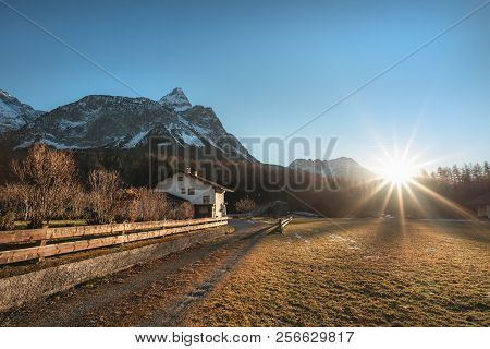 Early Winter Landscape With Dried Grass, Leafless Trees, The Austrian Alps Mountains And A Bright Su