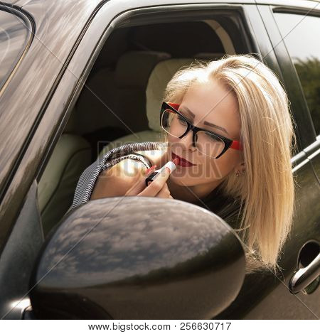 The Girl Paints Her Lips With Red Lipstick Look In The Mirror In The Sun Shade In Her Car. A Young W