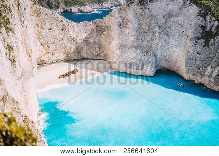 Navagio Beach With Turquoise Blue Sea Water Surrounded By Huge White Cliffs. Famous Landmark Locatio
