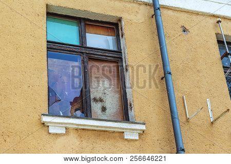 Broken Old Window Of The Building. Poor Quarter. Broken Glass In The Window. The Broken Window Is Co