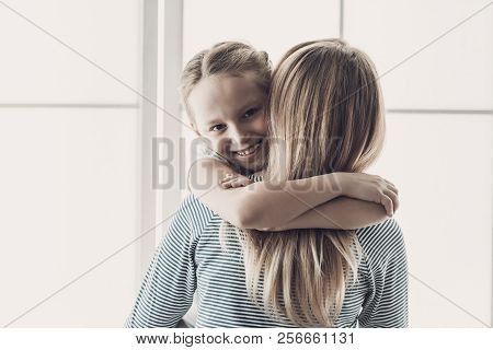 Young Mother And Smiling Little Daughter Hugging. Happy Adorable Little Girl Hugging Adult Woman Nea