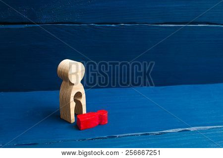 A Wooden Figure Of A Woman With A Void From Which A Red Child Fell. The Concept Of The Loss Of A Chi