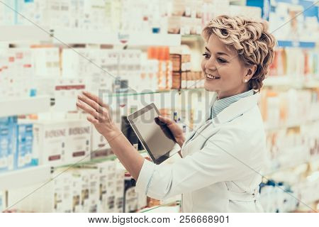 Mature Female Pharmacist At Work In Farmacy Store. Adult Pharmacist Wearing White Coat Holding Table