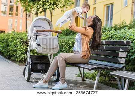 side view of mother holding happy baby on bench near stroller poster
