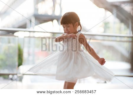 Happy adorable little girl in white dress dancing. Asian family outdoor lifestyle with natural light.