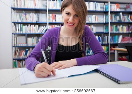 Portrait of a smiling young female student writing on a notebook in a library