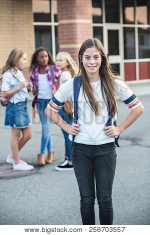 Cute hispanic pre-adolescent teen student hanging out with friends after school. Selective focus on the smiling girl student standing outside the school building