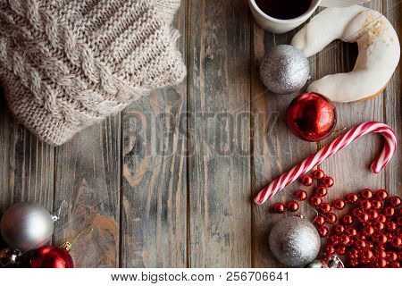 festive christmas decor background. seasonal design with holiday adornments and embellishments. knitted sweater shiny balls beads and candy cane on grey wooden backdrop. poster
