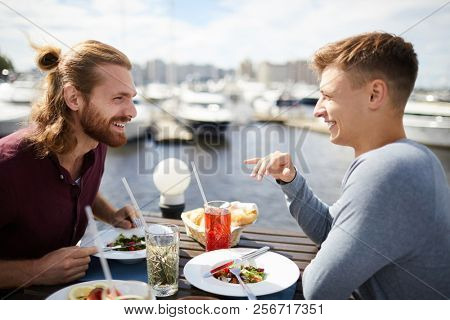 Two happy young buddies sitting by served table, talking and eating vegetarian lunch in outdoor cafe