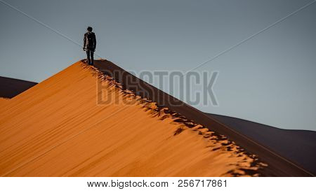 Young Male Traveler And Photographer Standing On The Top Of Sand Dune During The Sunrise In Namib De