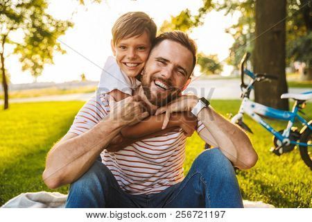 Laughing father and his son having fun together at the green park, sitting on a blanket, piggyback ride