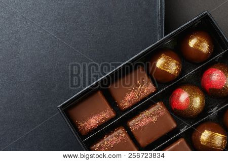 Set of luxury handmade bonbons in box on black background. Exclusive handcrafted chocolate candy. Product concept for chocolatier. Copy space poster