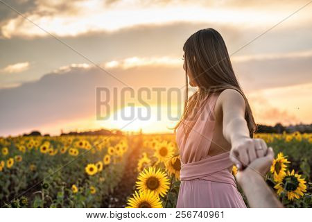 Boyfriend holding hands leading Girlfriend a field of flowers