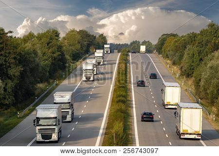 Trucks On The German Motorway,evening Traffic Of Cars On The Highway