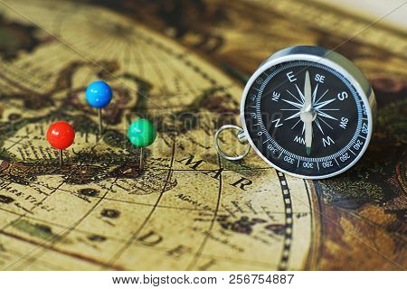 Compass and notebook on blur vintage world map, journey concept, copy space poster