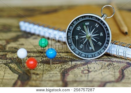 Compass, notebook and marking pins on blur vintage world map, journey concept, copy space poster