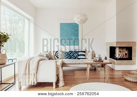 Turquoise Blue Knot Pillow On A Beige Corner Sofa And An Abstract Poster On A White Wall In A Modern