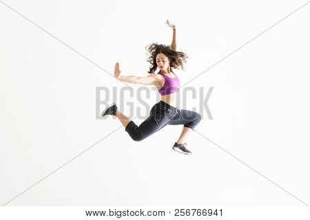 Enthusiastic Young Woman In Midair Practicing Ballet Moves Against White Background
