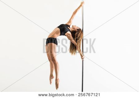 Ambitious Pole Dancer Showing Fitness And Strength While Rehearsing In Studio