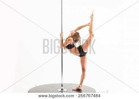 Full Length Of Confident Pole Dancer Stretching Legs To Split In Studio