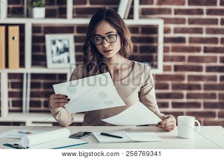 Young Beautifull Woman Upset With Paperwork. Beautiful Woman Wearing Glasses Sitting At Desk And Hol