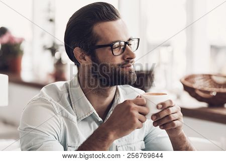 Young Handsome Man With Cup Of Coffee In Cafe. Portrait Of Smiling Bearded Man Wearing Glasses Relax