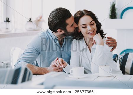 Young Couple Drinking Coffee Together At Home. Handsome Man Hugging And Kissing Beautiful Woman Sitt