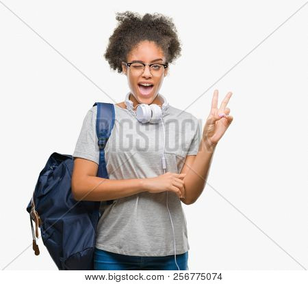 Young afro american student woman wearing headphones and backpack over isolated background smiling with happy face winking at the camera doing victory sign. Number two.