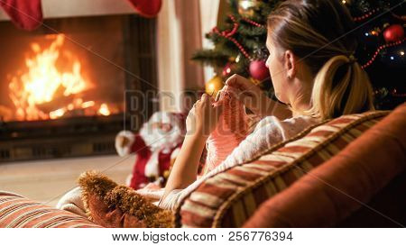 Toned Portrait Of Young Woman Knitting Socks In Armchair And Looking At Burning Fireplace