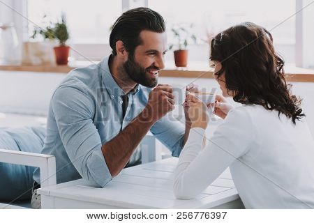 Young Couple Drinking Coffee Together At Home. Handsome Man Sitting At Table Next To Beautiful Woman