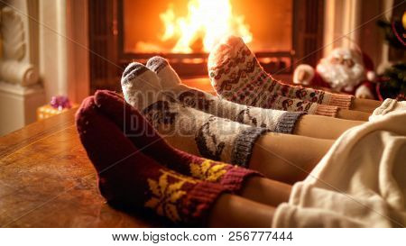 Young Family Wearing Warm Woolen Socks And Lying Under Blanket Relaxing At Fireplace
