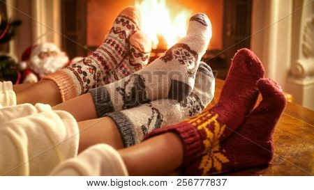 Family Wearing Knitted Woolen Socks Warming Feet At Fireplace On Christmas Eve