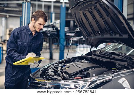 Auto Car Repair Service Center. Mechanic Examining Car Engine