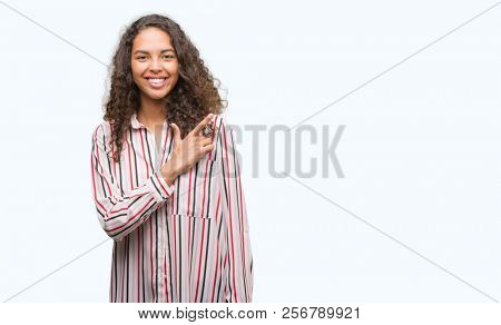 Beautiful young hispanic woman cheerful with a smile of face pointing with hand and finger up to the side with happy and natural expression on face looking at the camera.