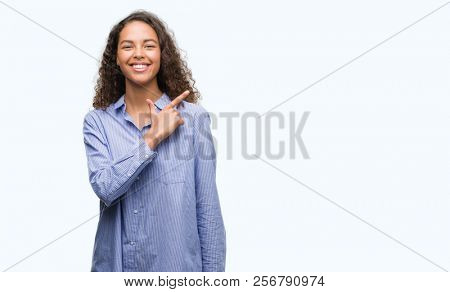 Young hispanic business woman cheerful with a smile of face pointing with hand and finger up to the side with happy and natural expression on face looking at the camera.