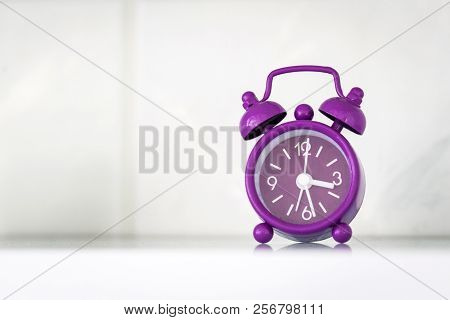 Purple Alarm Clock In A Bright Room Showing The Time