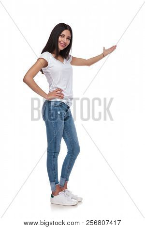 confident casual woman in white t-shirt recommends to side while standing on white background and smiling, full length picture