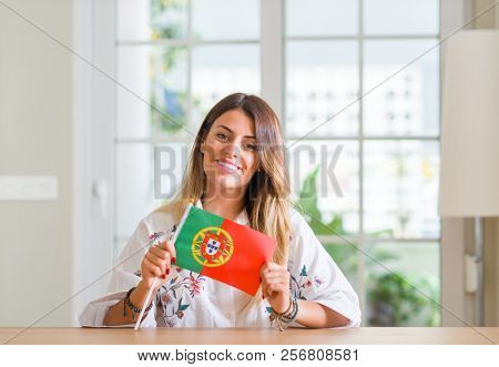 Young woman at home holding flag of Portugal with a happy face standing and smiling with a confident smile showing teeth