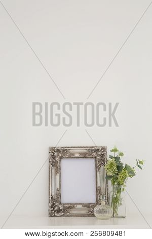 Picture frame, perfume bottle and flora on table against white wall