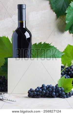 Bottle Of Red Mulled Wine Mockup For Your Logotype, White Paper Card For Text, Copyspace. Red Grapes