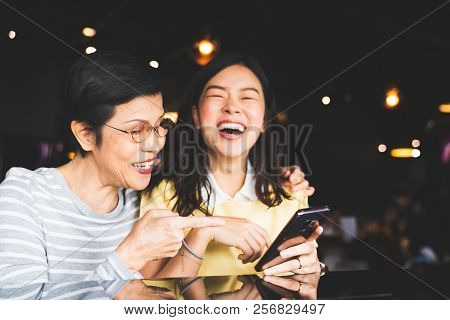 Asian Mother And Daughter Laughing And Smiling On A Selfie Or Photo Album, Using Smartphone Together
