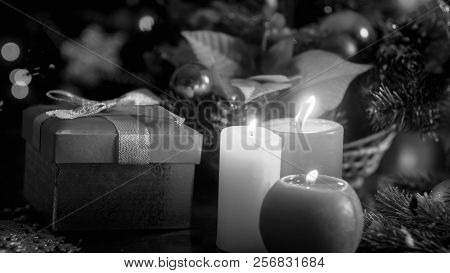 Black And White Image Of Three Burning Candles And Christmas Gifts On Wooden Background