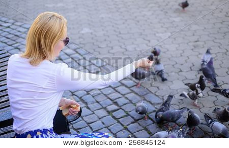 Girl Feeding Dove Birds Urban Background. Girl Blonde Woman Relaxing City Square And Feeding Pigeons
