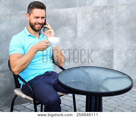 Coffee Break Brings Physical And Mental Wellbeing. Man Sit Terrace And Drink Cappuccino Speak Phone
