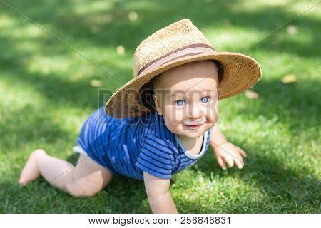 Portrait Cute Funny Little Boy In Big Straw Hat Having Fun On Green Grass Lawn At Park. Sweet Little
